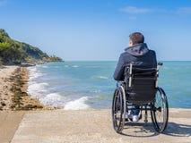 Para trás do homem deficiente na cadeira de rodas na praia foto de stock royalty free