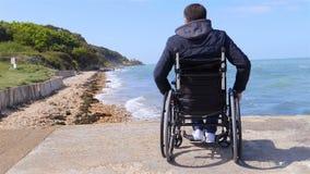 Para trás do homem deficiente na cadeira de rodas no movimento lento da praia vídeos de arquivo