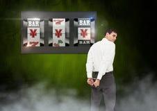 Para trás do homem que olha o slot machine do casino com mão cuffs fotografia de stock royalty free