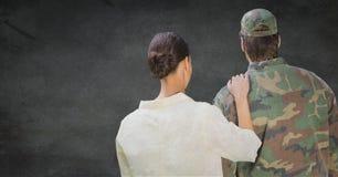 Para trás do soldado e da esposa contra a parede cinzenta com folha de prova do grunge imagens de stock royalty free