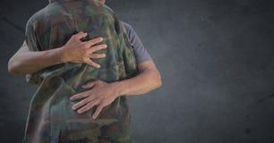 Para trás do soldado que abraça contra o fundo cinzento com folha de prova do grunge fotografia de stock