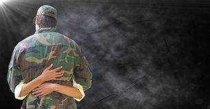 Para trás do soldado que está sendo abraçado contra o fundo preto do grunge com alargamento foto de stock royalty free