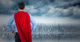 Para trás do super-herói do homem de negócio com mãos nos quadris contra a skyline Foto de Stock