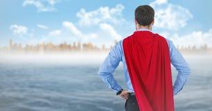 Para trás do super-herói do homem de negócio com mãos nos quadris contra a skyline e a água Fotos de Stock Royalty Free
