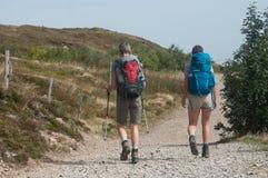 Para trekkers chodzi przy wierzchołkiem z plecakiem Fotografia Stock