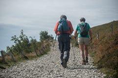 Para trekkers chodzi przy wierzchołkiem z plecakiem Zdjęcie Royalty Free