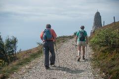 Para trekkers chodzi przy wierzchołkiem z plecakiem Obraz Royalty Free