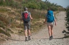 Para trekkers chodzi przy wierzchołkiem z plecakiem Obraz Stock
