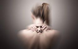 Para trás de uma mulher que indica a dor de pescoço Foto de Stock