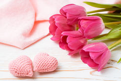 Para trykotowi różowi serca i bukiet świezi tulipany na drewnianym stole obraz stock