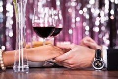 Para trzyma each - inny ręka przy gościem restauracji Obrazy Royalty Free