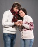 Para trzyma filiżankę kawy na szarym tle Zdjęcia Stock