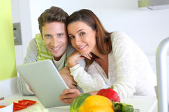 Para używa cyfrową pastylkę w kuchni Fotografia Royalty Free