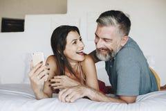 Para używa smartphone w łóżku zdjęcia royalty free