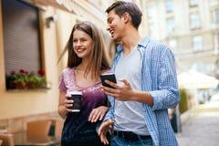 Para Używa telefon komórkowego I Pijący kawę Outdoors Obrazy Royalty Free