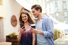 Para Używa telefon komórkowego I Pijący kawę Outdoors Zdjęcia Stock