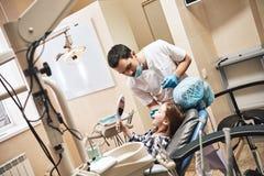 Para um sorriso da estrela mundial Crian?a no escrit?rio dental O dentista explica a seu paciente como escovar os dentes imagem de stock
