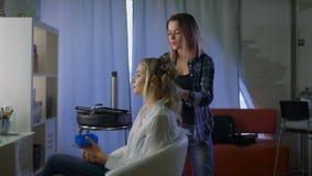 Para una mujer rubia hermosa joven en un salón de belleza que hace estilo de pelo Una muchacha y un peluquero almacen de metraje de vídeo