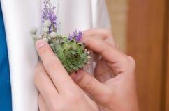 Para unir uma casa de botão do casamento a um revestimento Imagem de Stock Royalty Free