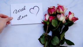 Para usted tarjeta, regalo y flores de felicitación en el tablero blanco, visión superior almacen de metraje de vídeo
