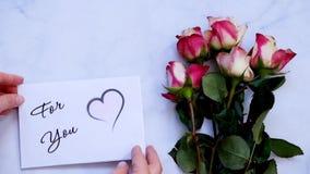 Para usted tarjeta y flores de felicitación en el tablero blanco, visión superior metrajes