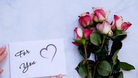 Para usted tarjeta y flores de felicitación en el tablero blanco, visión superior almacen de metraje de vídeo