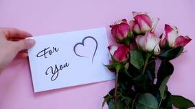 Para usted tarjeta y flores de felicitación en el tablero rosado, visión superior almacen de video