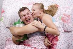 Para w łóżku: z baryłką piwo, ona próbuje brać daleko od Zdjęcia Royalty Free
