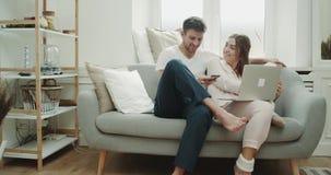 Para w żywym pokoju w ranku robi rozkazowi używać telefon i notatnik, siedzi na są w piżamach zbiory wideo
