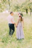 Para w miłości chodzi outdoors trzymający ręki, atrakcyjnego młodego człowieka i kobiety jest ubranym wianek na dacie, patrzeje e obrazy royalty free