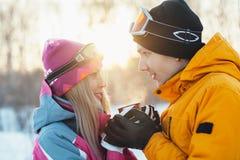 Para w miłości cieszy się napój w świetle słonecznym, mężczyzna i kobiecie pije herbaty backlit, filiżanka w zima lesie Obraz Stock