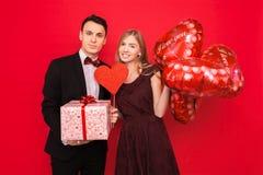 Para w miłości, mężczyzna i kobieta, dajemy innym prezentom each, trzymający prezentów pudełka i balony, na czerwonym tło walenty fotografia stock