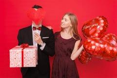 Para w miłości, mężczyzna i kobieta, dajemy innym prezentom each, trzymający prezentów pudełka i balony, na czerwonym tło walenty obrazy stock
