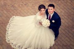 Para w miłości państwie młodzi Widok od above na tle bruk płytka Duży oblamowanie bridal biel suknia z koronką zdjęcie stock