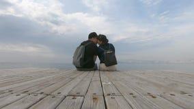 Para w miłości siedzi na drewnianym molu ślicznym opowiadać i, podziwia dennego widok Pi?kny timelapse zbiory