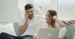Para w ranku robi rozkazowi od telefonu i ogląda na notatniku są szczęśliwym obsiadaniem na kanapie wewnątrz zdjęcie wideo