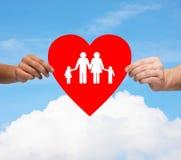 Para wręcza mieniu czerwonego serce z rodziną Fotografia Stock