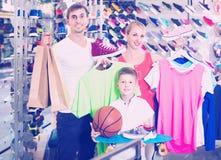Para z chłopiec wybiera buty w sporta sklepie Fotografia Royalty Free