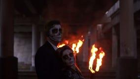 Para z czaszka makijażem na tle palenie dym i ogień halloween zbiory