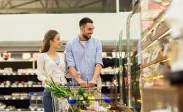 Para z jedzeniem w wózek na zakupy przy sklepem spożywczym Zdjęcie Stock