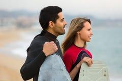 Para z kipieli deskami na plaży Zdjęcia Royalty Free