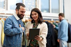 Para z pastylka komputerem osobistym przy rocznika sklepem odzieżowym Zdjęcie Stock