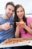 Para z pizzą i TV pilotem Zdjęcie Royalty Free
