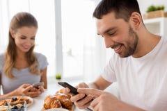 Para z smartphones ma śniadanie w domu Zdjęcia Royalty Free