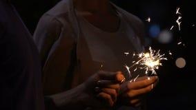 Para zaświeca Bengal ogienia, robi życzy przy Ciosałem roku nocą, wakacyjna magia zdjęcie wideo