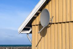 Parabola receiver. Parabola satellite receiver on a wooden yellow house wall close to the sea in Denmark Stock Image