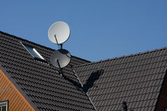 Parabolic antenna. An old house and an old aerial Royalty Free Stock Images