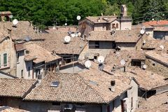 Parabolic antenna. S on the houses roof at the Castell'Arquato, the medieval town located on the first hills on the Val D'Arda in the province of Piacenza, Italy Stock Images