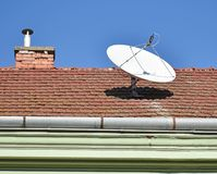 Parabolic antenna on the roof of a house. Outdoor stock photo