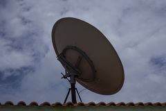 Parabolic dish antenna held on the roof top of a building. Dish is used by consumers to receive direct-broadcast satellite televi. Parabolic dish antenna held on royalty free stock images